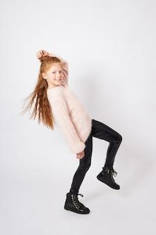 Petite fille sourit. enfant en vêtements d'automne pose sur blanc