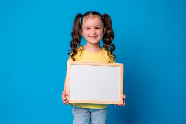 Petite fille sourit et est titulaire d'un tableau de dessin vide sur bleu