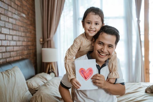 Petite fille sourit étreignant son père par derrière tout en tenant un symbole en papier du cœur