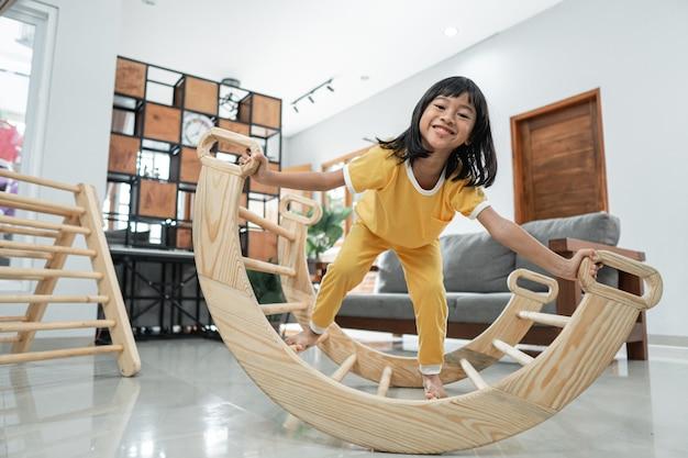 Petite fille sourit en jouant à l'équilibre dans un jouet triangle pikler à la maison