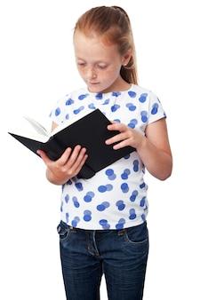Petite fille studieuse lisant un livre