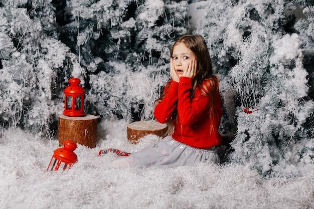 Petite fille surprise assis près de l'arbre de noël