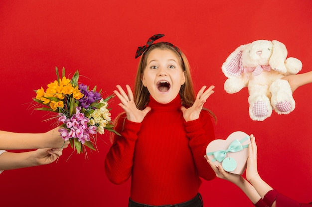 Petite fille surprise et étonnée recevant beaucoup de cadeaux pour la saint-valentin