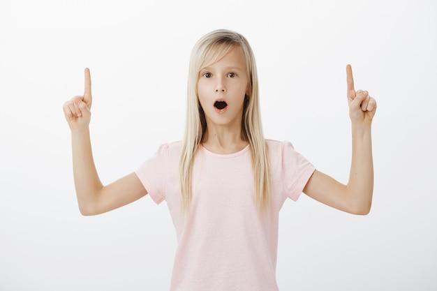 Petite fille surprise et impressionnée pointant vers le haut
