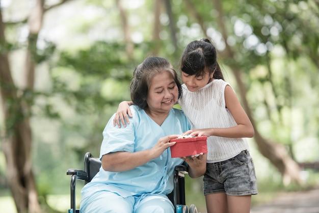 La petite-fille a la surprise de voir sa grand-mère assise sur un fauteuil roulant.