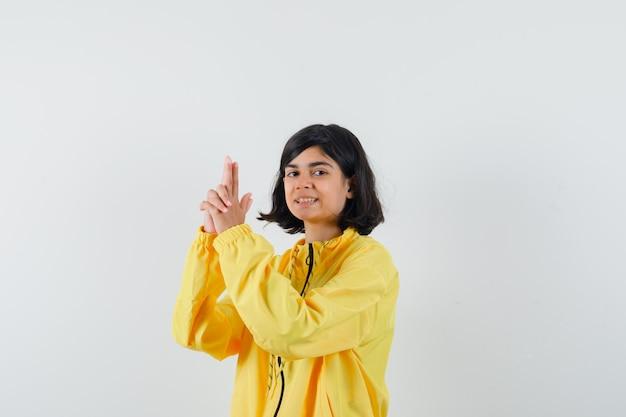 Petite fille en sweat à capuche jaune montrant le geste du pistolet et l'air confiant, vue de face.