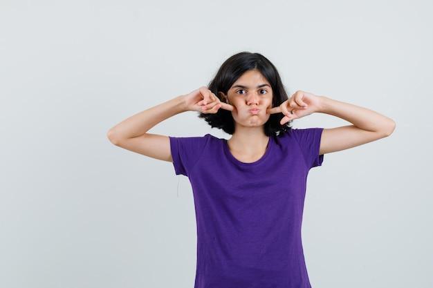 Petite fille en t-shirt en appuyant sur les doigts sur les joues soufflées,