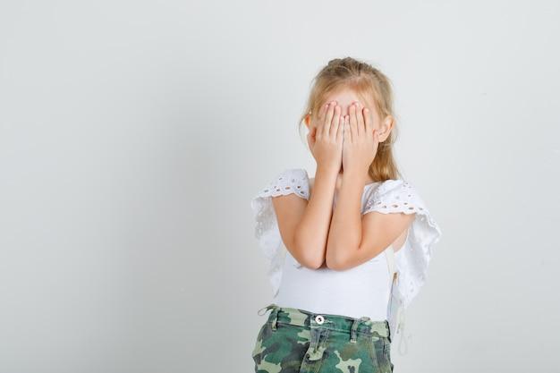 Petite fille en t-shirt blanc, jupe couvrant les yeux avec les mains