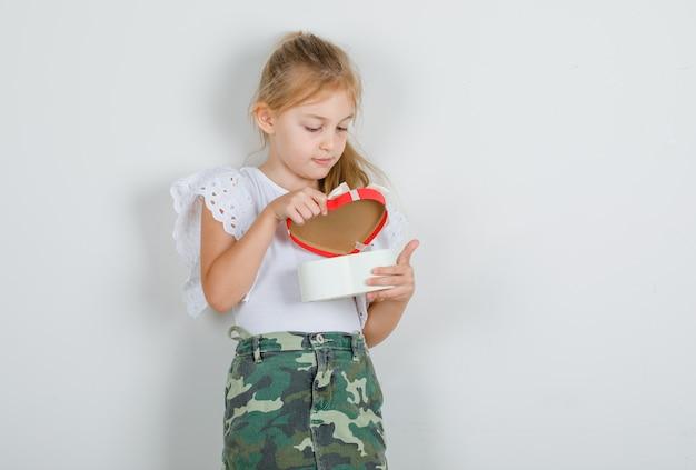Petite fille en t-shirt blanc, jupe ouvrant la boîte présente et à la prudence