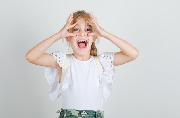 Petite fille en t-shirt blanc, jupe ouvrant les yeux avec les doigts et à la drôle