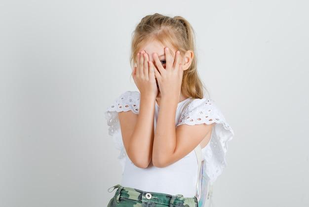 Petite fille en t-shirt blanc, jupe regardant à travers les doigts avec un œil