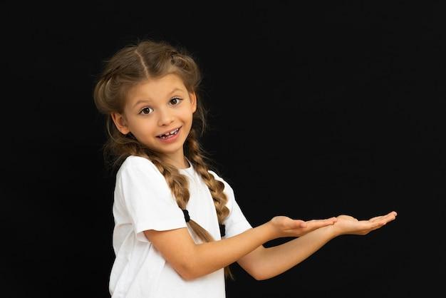 Une petite fille en t-shirt blanc montre votre annonce.