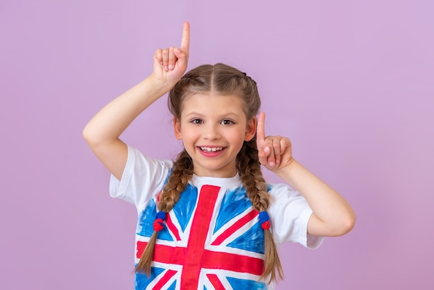 Petite fille en t-shirt du drapeau de la grande-bretagne pointe vers le haut sur fond violet clair