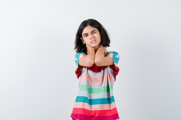 Petite fille en t-shirt, jeans tenant les mains sur le cou, ayant des douleurs au cou et l'air épuisé, vue de face.