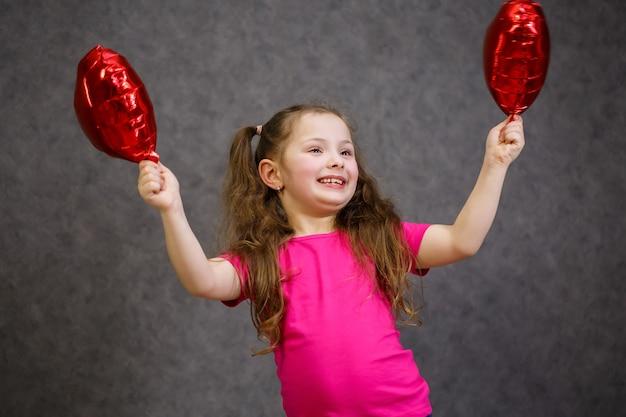 Petite fille en t-shirt rose joue avec des ballons