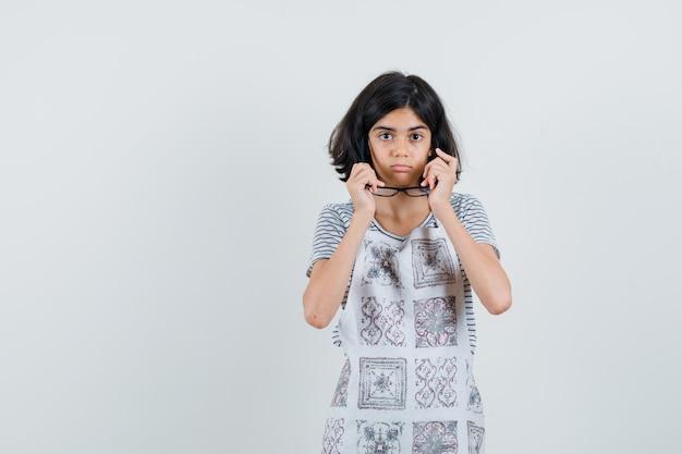 Petite fille en t-shirt, tablier, décoller les lunettes et à la perplexité,