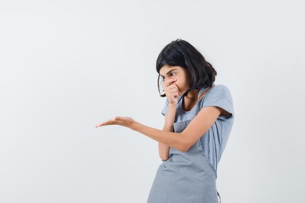 Petite fille en t-shirt, tablier étirant la main de manière interrogative et à la surprise, vue de face.