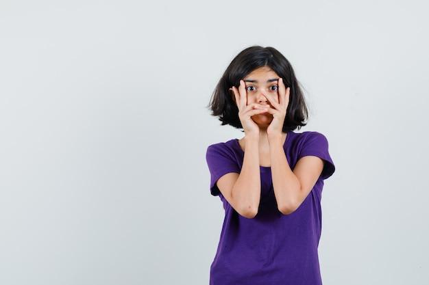 Petite fille en t-shirt tenant les mains sur le visage et à la surprise,