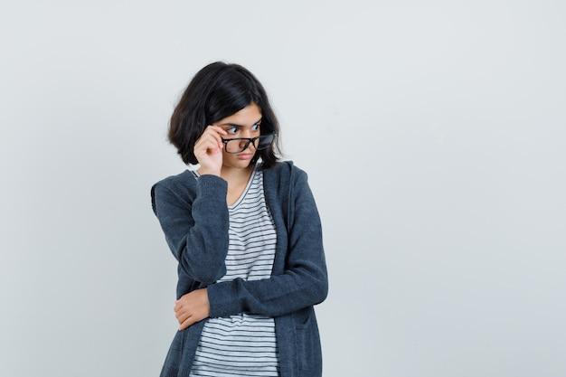 Petite fille en t-shirt, veste décollant des lunettes et à la surprise,