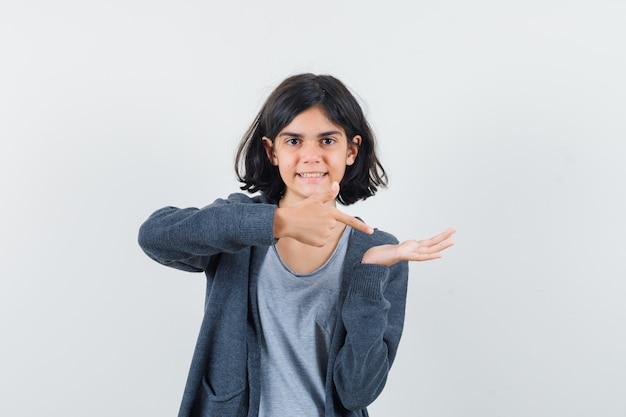 Petite fille en t-shirt, veste pointant sur sa paume vide et regardant confiant, vue de face.