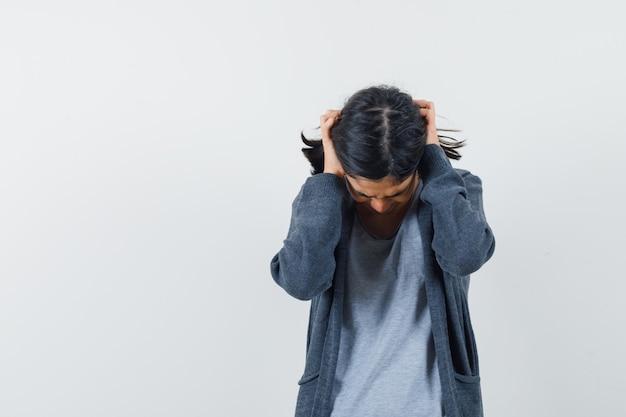 Petite fille en t-shirt, veste tenant les mains sur les oreilles et regardant irrité, vue de face.