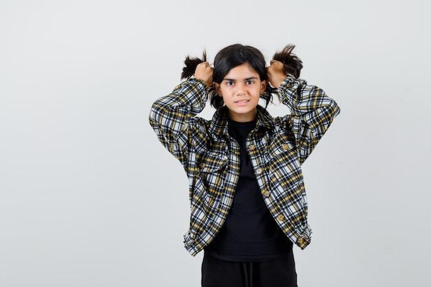 Petite fille en t-shirt, veste tenant une mèche de cheveux et semblant mignonne, vue de face.