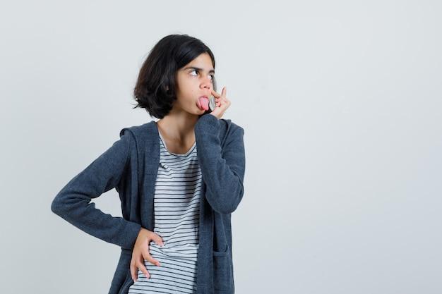 Petite fille en t-shirt, veste tirant la paupière, qui sort la langue,