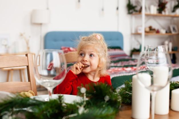Petite fille à la table de noël, manger des biscuits en pain d'épice