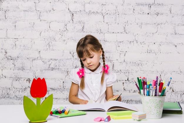 Petite fille à la table en train de faire ses devoirs