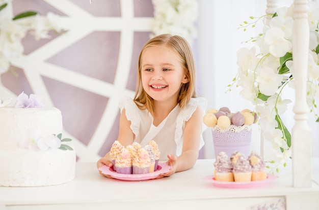 Petite fille tenant une assiette rose avec des gâteaux sucrés dans la barre chocolatée