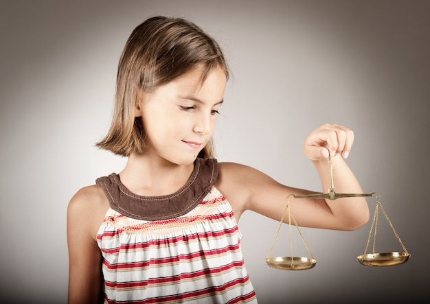 Petite fille tenant la balance de la justice