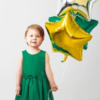 Petite fille tenant des ballons en forme d'étoiles