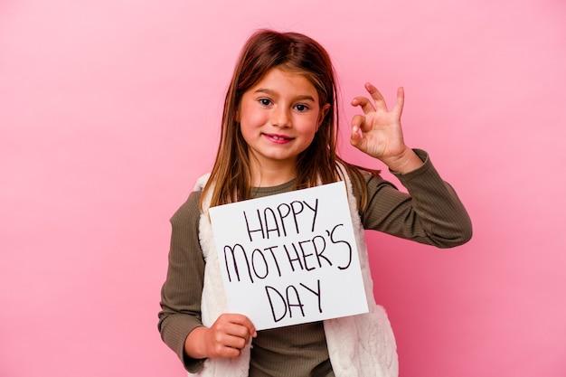 Petite fille tenant une bannière de fête des mères heureuse isolée sur fond rose