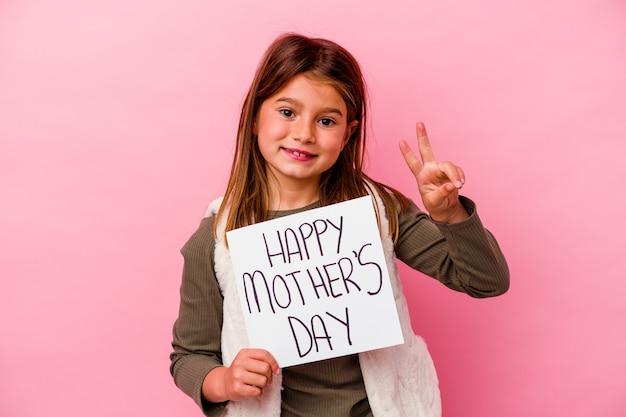 Petite fille tenant une bannière de fête des mères heureuse isolée sur un mur rose