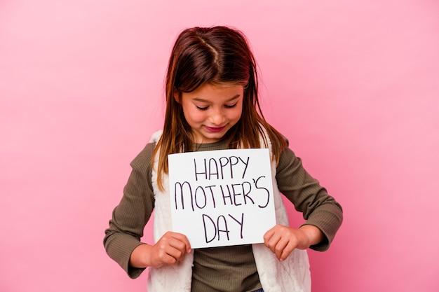 Petite fille tenant une bannière de fête des mères heureuse isolée sur rose