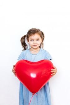 Petite fille tenant un beau ballon en forme de coeur rouge pour un cadeau pour la saint valentin, les amoureux, la saint valentin, la famille et le coeur