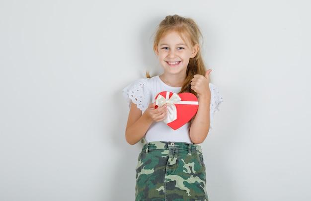 Petite fille tenant une boîte-cadeau avec le pouce vers le haut en t-shirt blanc