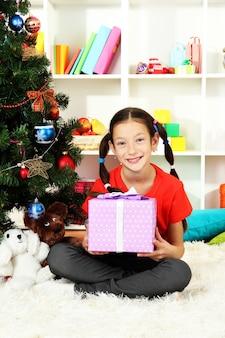 Petite fille tenant une boîte-cadeau près de l'arbre de noël