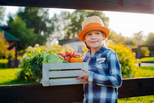 Petite fille tenant une boîte de légumes biologiques frais