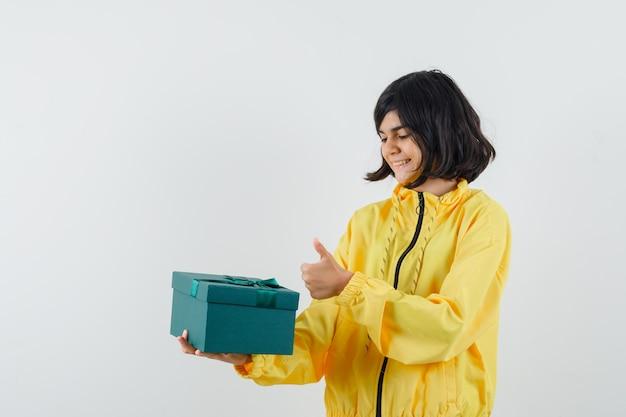 Petite fille tenant la boîte présente, montrant le pouce vers le haut en sweat à capuche jaune et regardant joyeux, vue de face.
