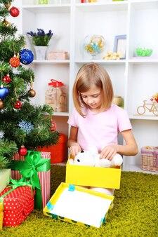 Petite fille tenant une boîte présente près de l'arbre de noël dans la chambre