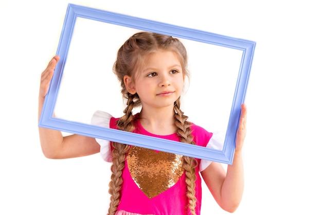 Petite fille tenant un cadre photo.