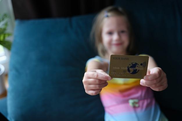 Petite fille tenant une carte bancaire de crédit en plastique à la maison en gros plan