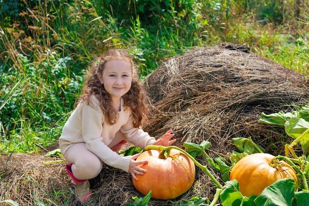 Petite fille tenant une citrouille sur un potiron