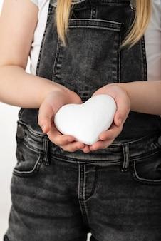 Petite fille tenant un coeur blanc dans ses mains. fille se dresse sur un fond blanc isolé