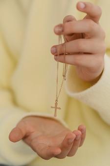 Petite fille tenant un collier croix