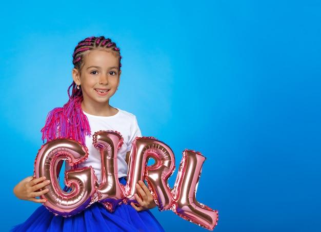 Petite fille tenant dans les mains des ballons avec l'inscription girl, sur l'espace bleu, avec espace copie.