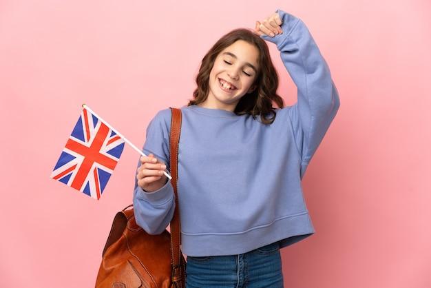 Petite fille tenant un drapeau du royaume-uni isolé sur fond rose célébrant une victoire