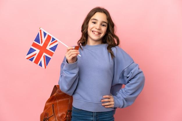 Petite fille tenant un drapeau du royaume-uni isolé sur fond rose posant avec les bras à la hanche et souriant