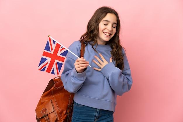 Petite fille tenant un drapeau du royaume-uni isolé sur fond rose souriant beaucoup